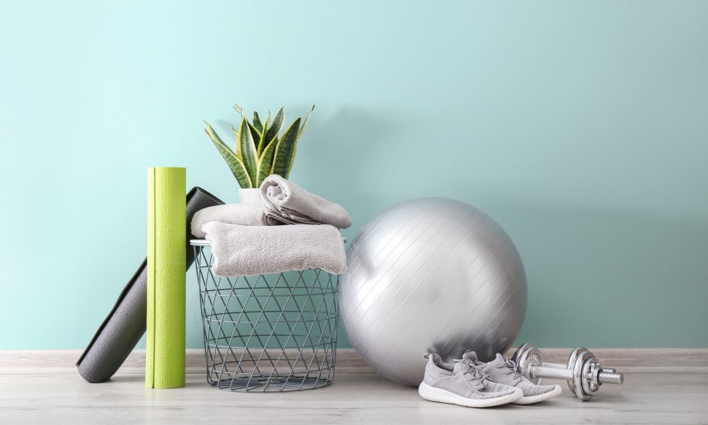 Set of sports equipment with fitness ball, towels and shoes near wall